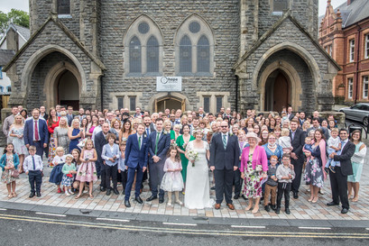 a large group shot of all guests stood outside a swansea church wedding