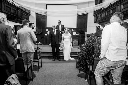 happy couple face their guests in a black and white wedding photograph