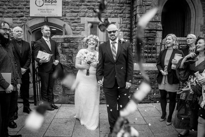 black and white wedding photograph of bride and groom showered in confetti