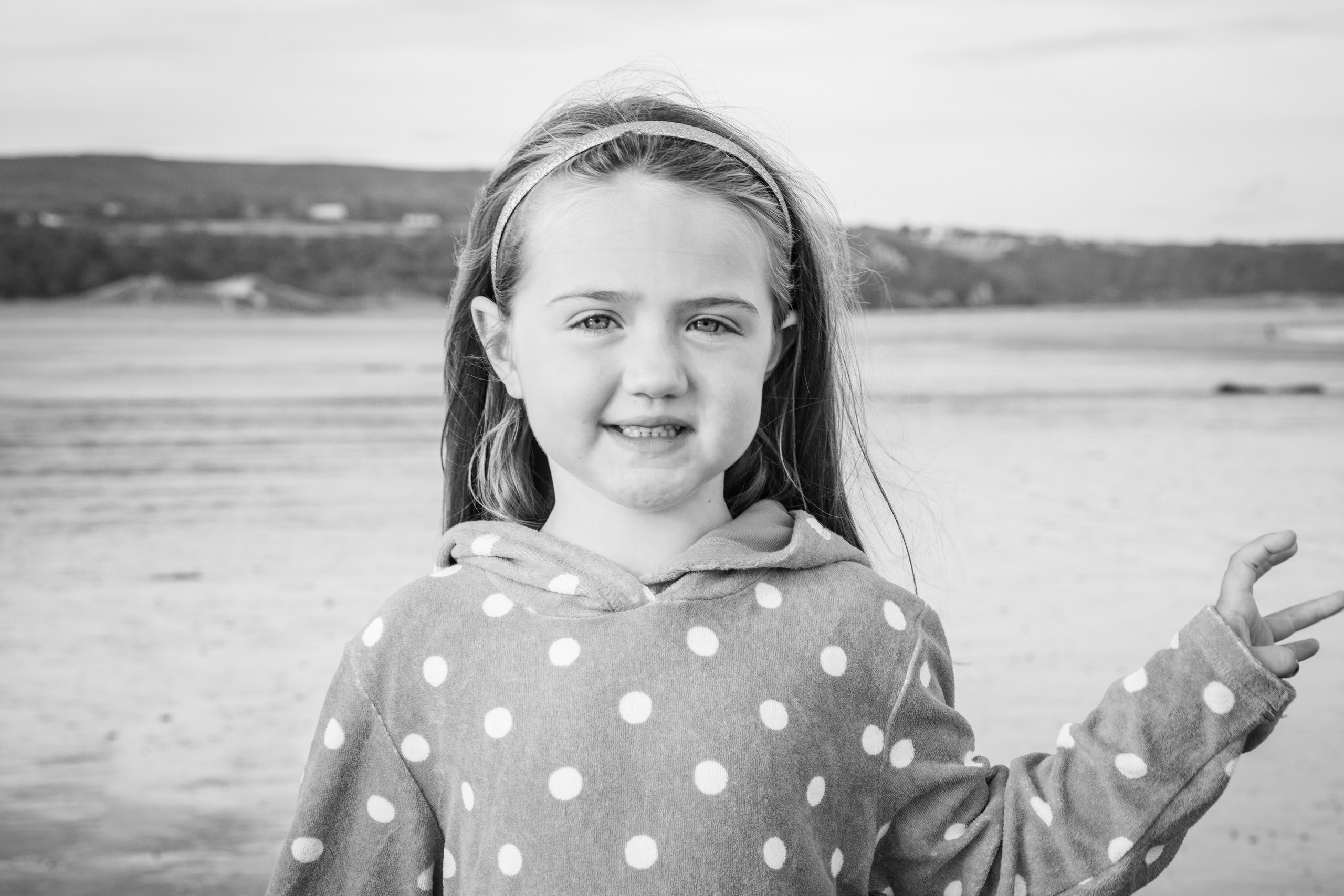 natural family portrait of a girl on the beach of Oxwich
