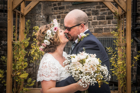 bride and groom embrace for a kiss for their wedding photos