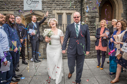 happy couple walking through confetti thrown by wedding guests outside gower church