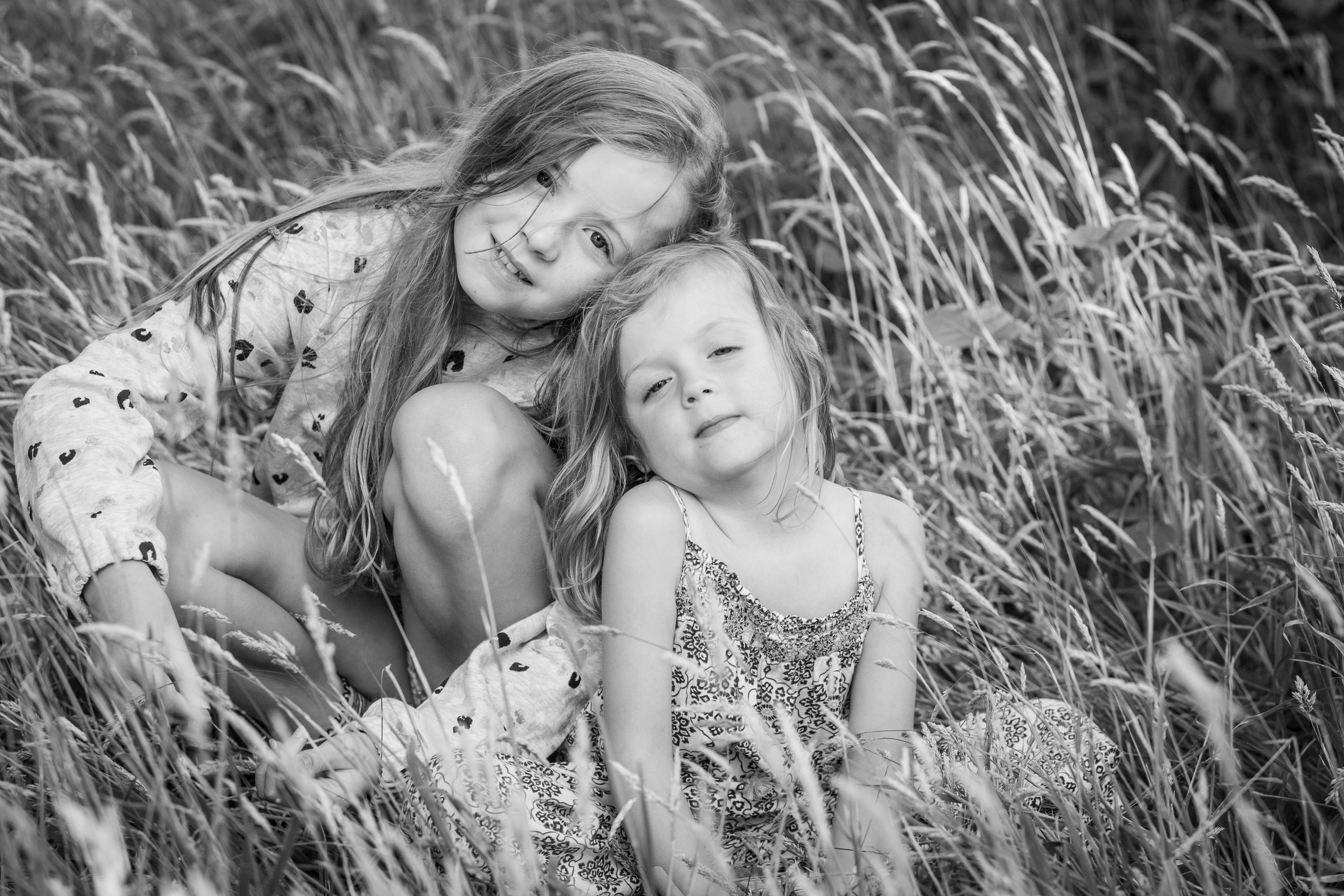 two sisters pose in a grass field in swansea