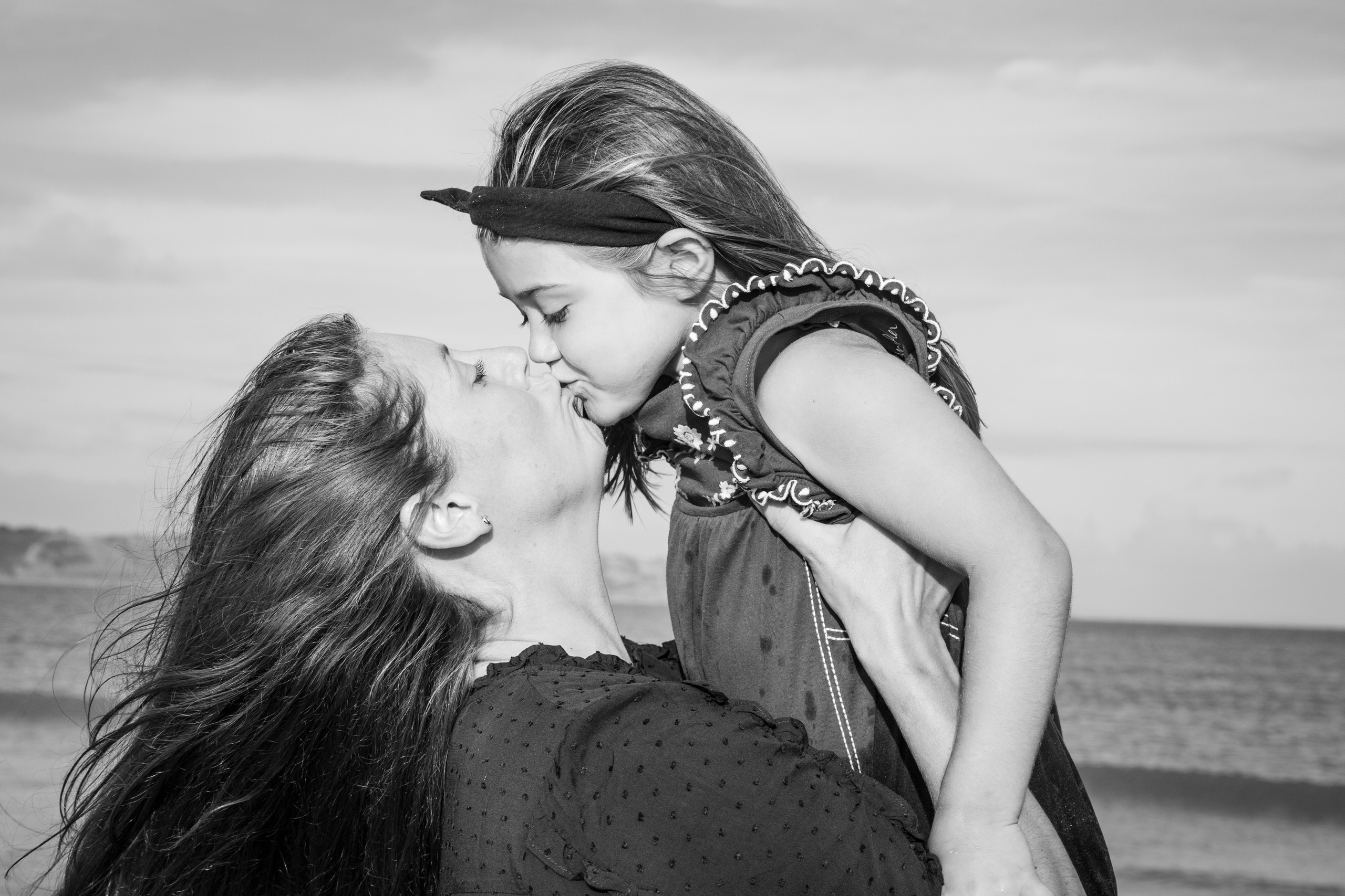sea front kiss between mother and daughter on oxwich bay in swansea