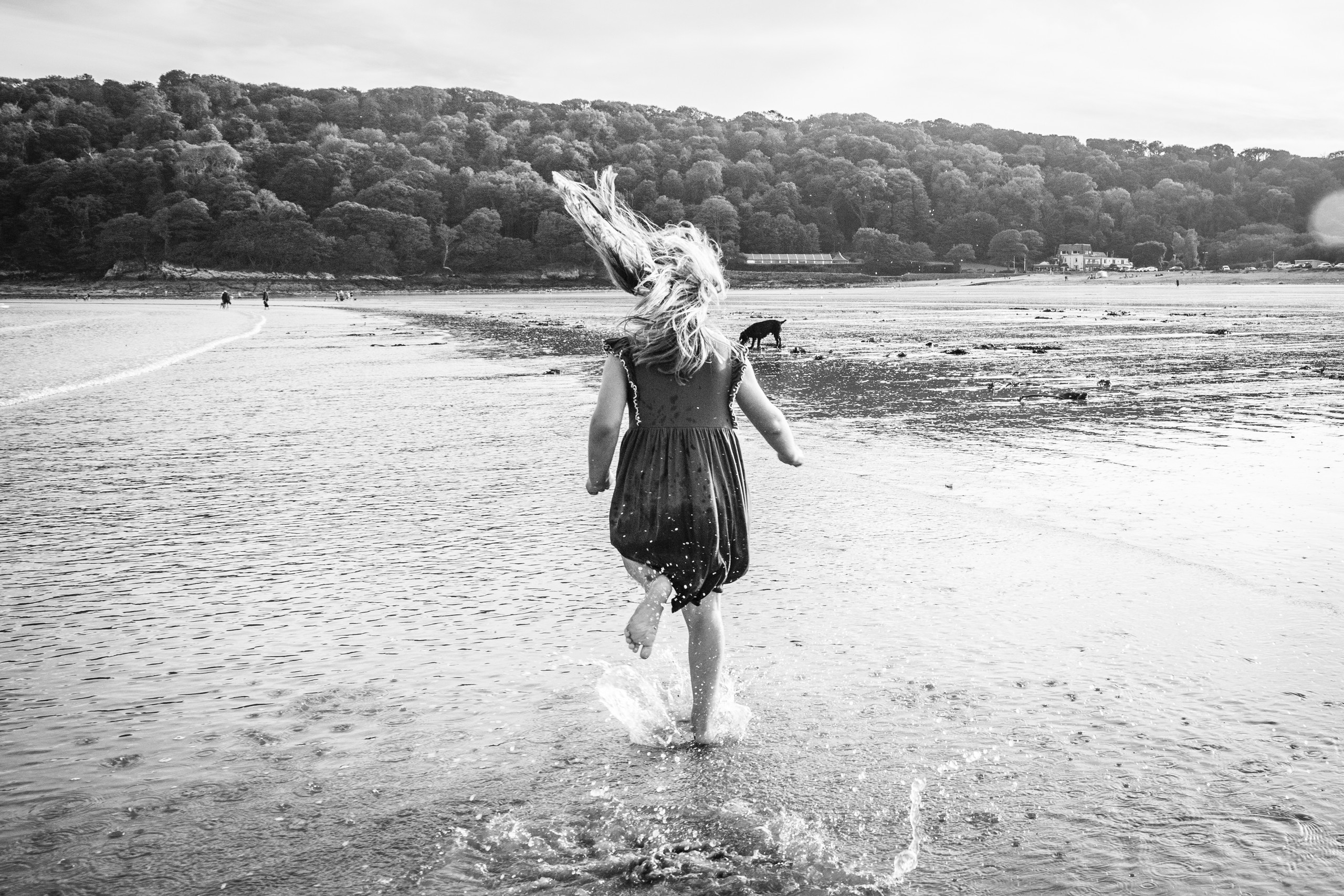 girl runs through the shore outside oxwich bay hotel