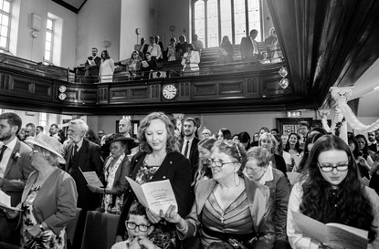 black and white wedding photography as guests sing hymns in swansea