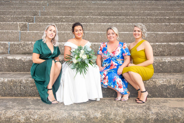 bride with her bridal party sat on the steps of swansea bay