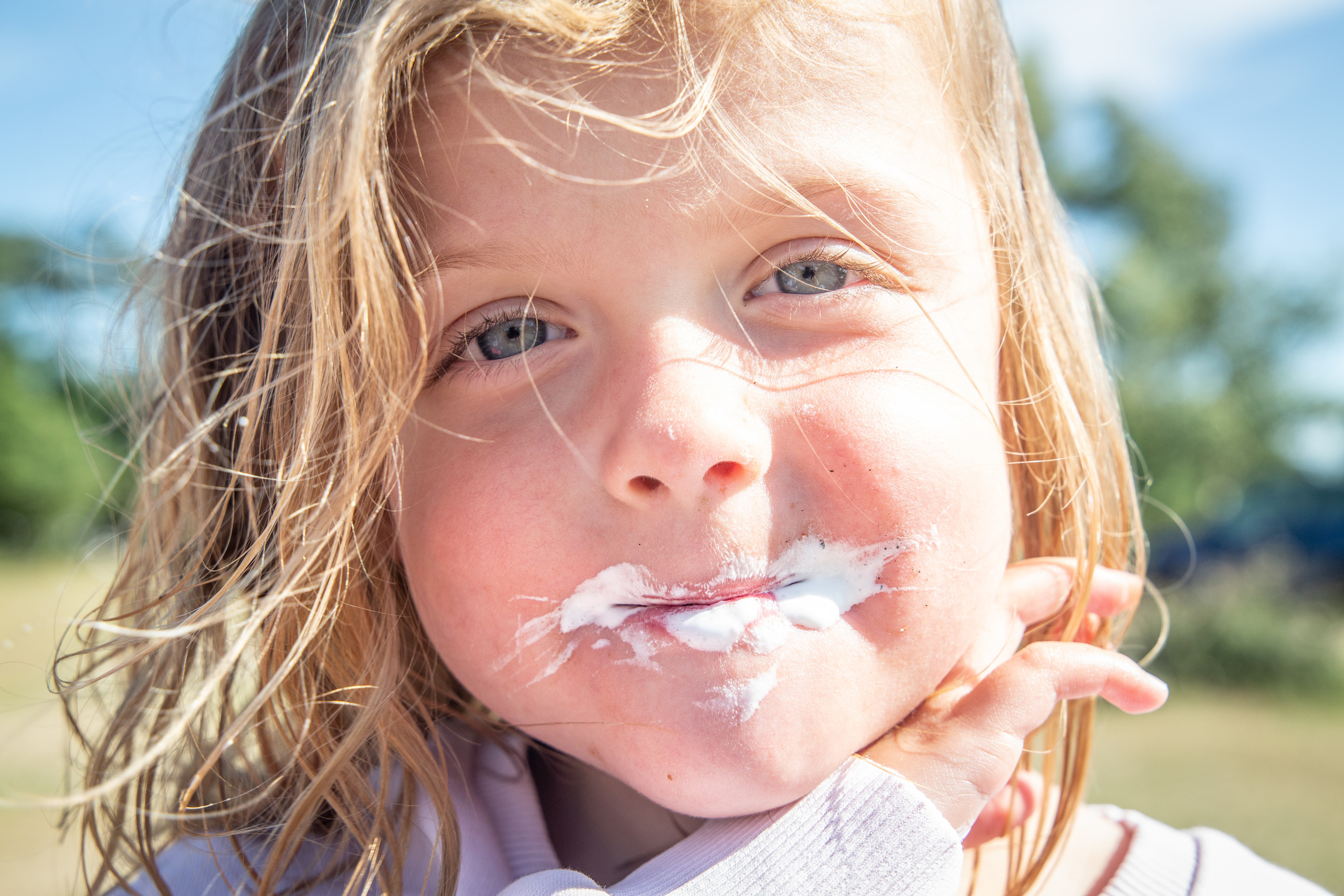 Joe's ice cream all over a child's face as she poses in swansea