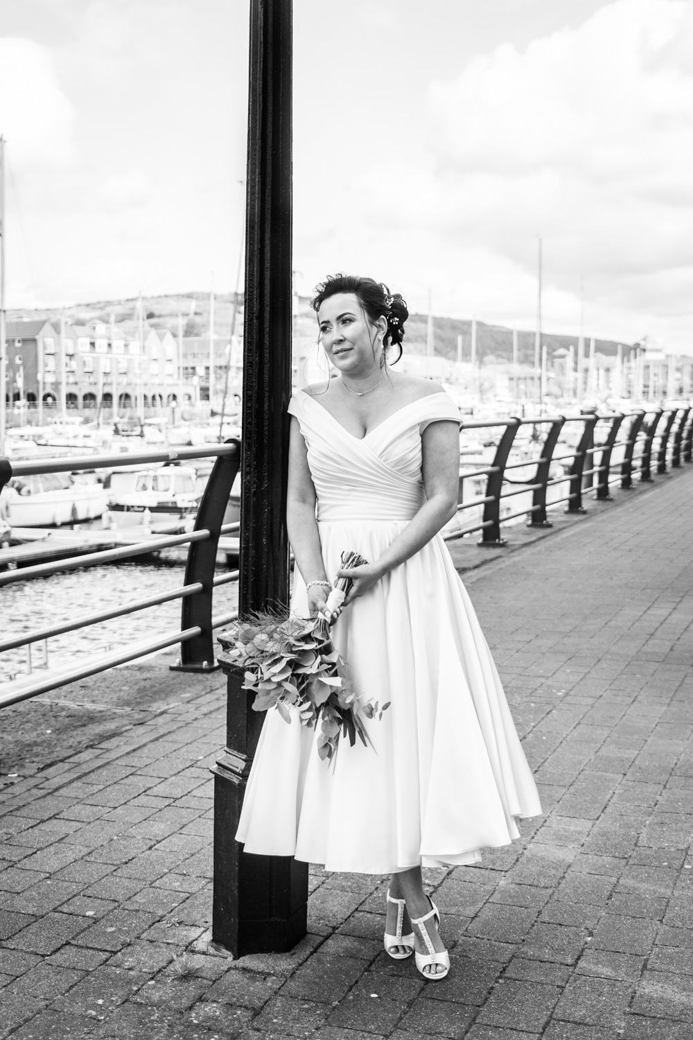 bride leaning against a lamp post in swansea marina