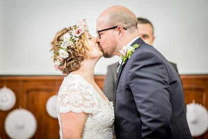 bride and groom share their first kiss inside a swansea church