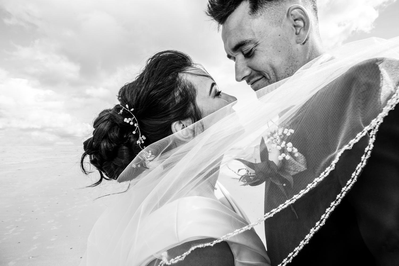 documentary wedding photography of bride and groom embracing on swansea beach
