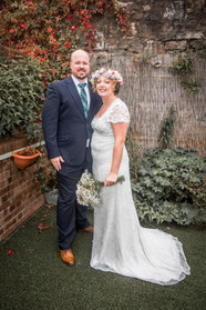 bride and groom pose for wedding photographer in swansea garden