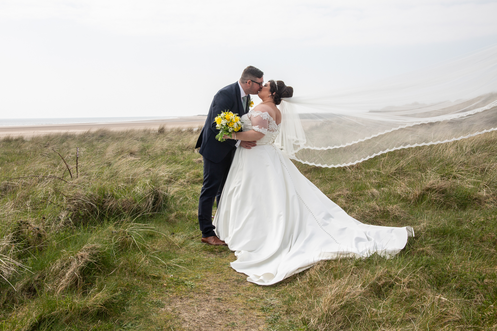 Burry Port Lighthouse Wedding Kissing Bride and Groom Photography. A Beach Wedding Portrait. Photographer covering The Gower, Carmarthenshire, Llanelli, South Wales and Bridgend