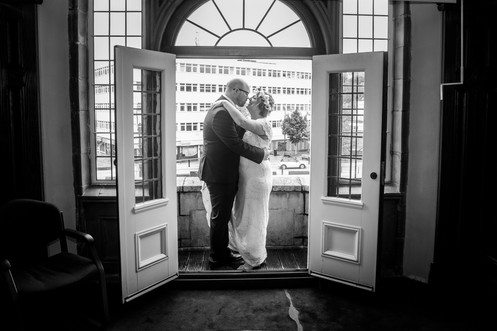 couple embrace in a black and white wedding photo overlooking swansea and the gower