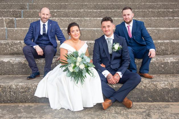groomsmen and bride sat on steps at swansea bay