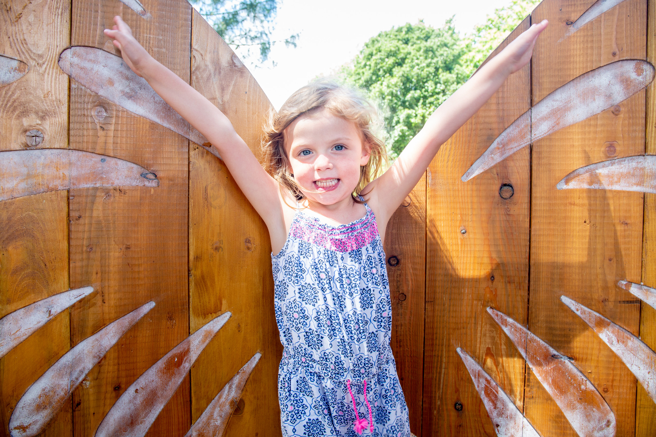 a happy girl stretches and poses in front of a butterfly sculpture for the photographer in a gower park
