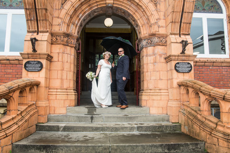 bride and groom photographed outside their swansea venue in the gower