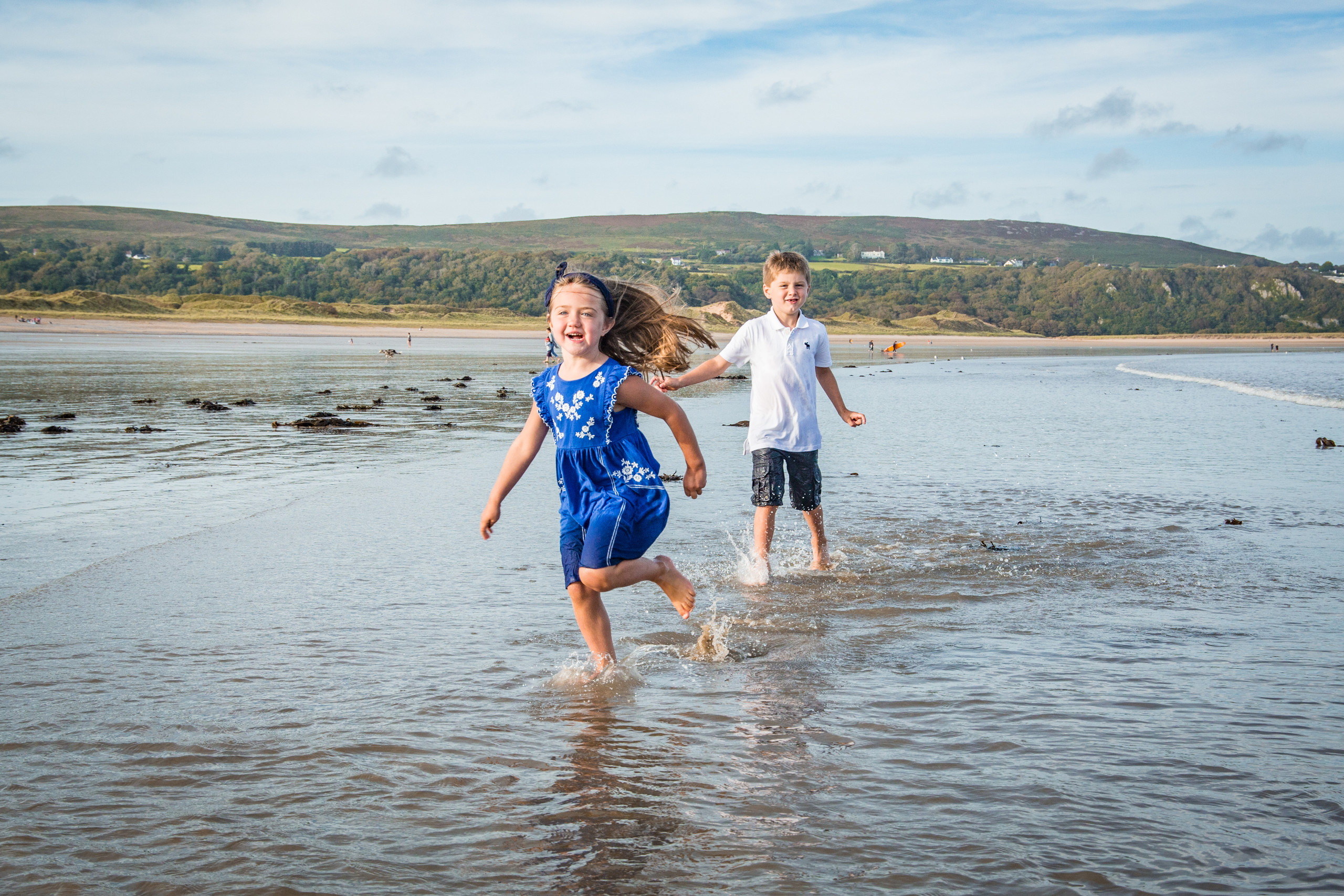 siblings play in the surf on a gower beach photo shoot
