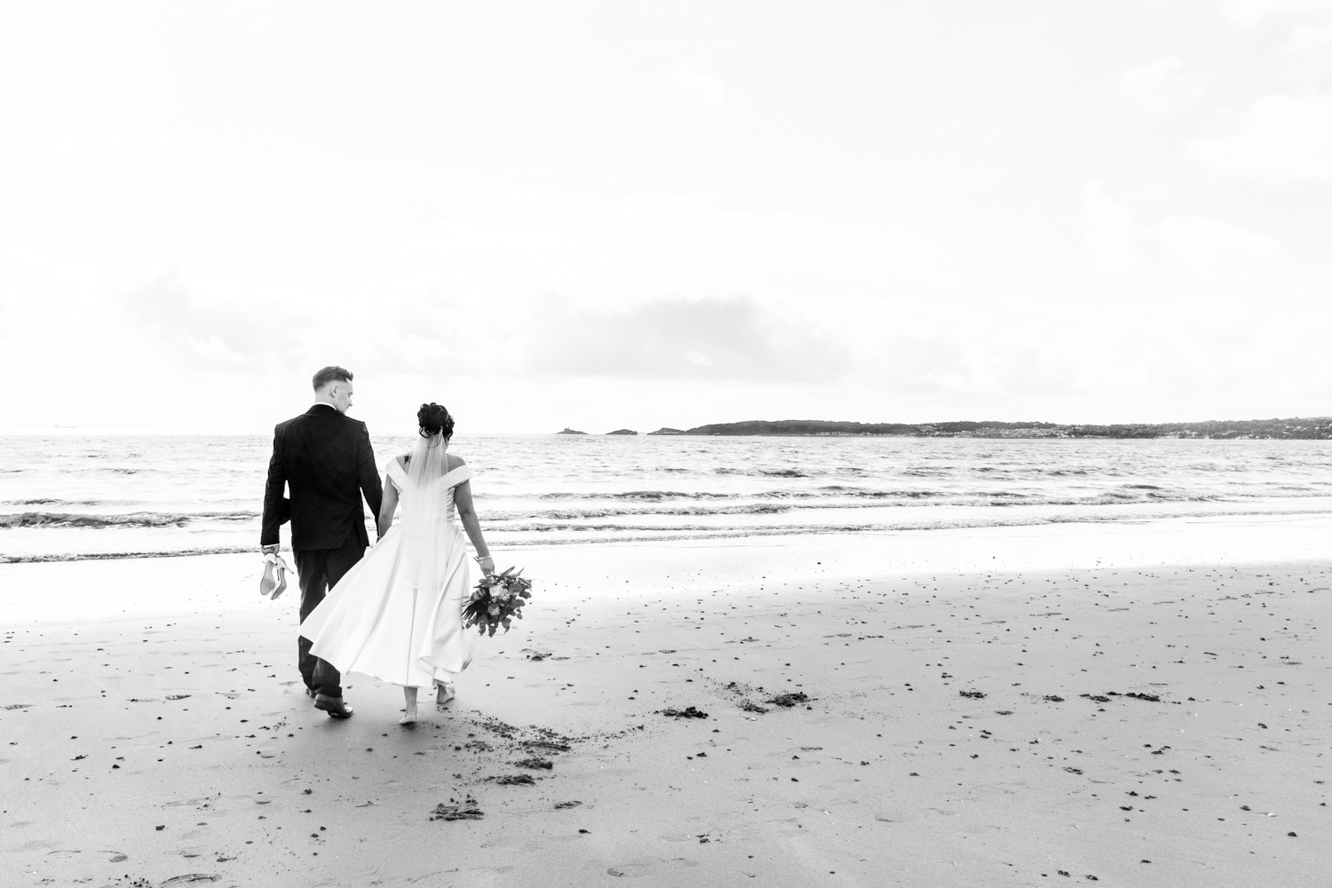 wedding photography of bride and groom on swansea bay with mumbles in the background