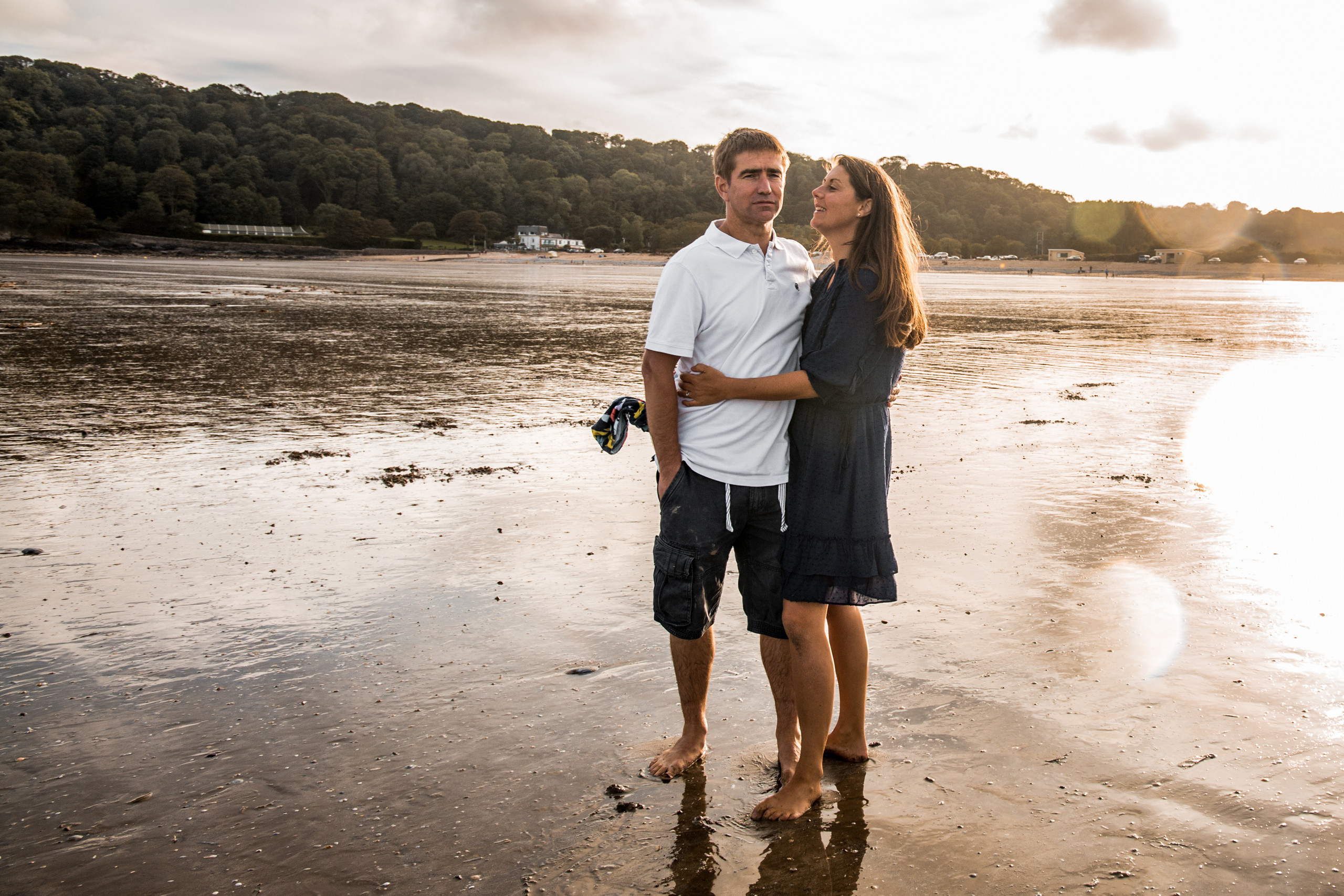 husband and wife embrace in the sunset at oxwich bay