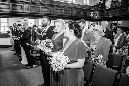black and white wedding photograph of guests singing in swansea church