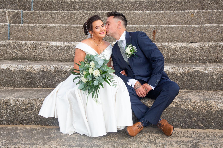 bride and groom pose on Swansea bay wedding steps