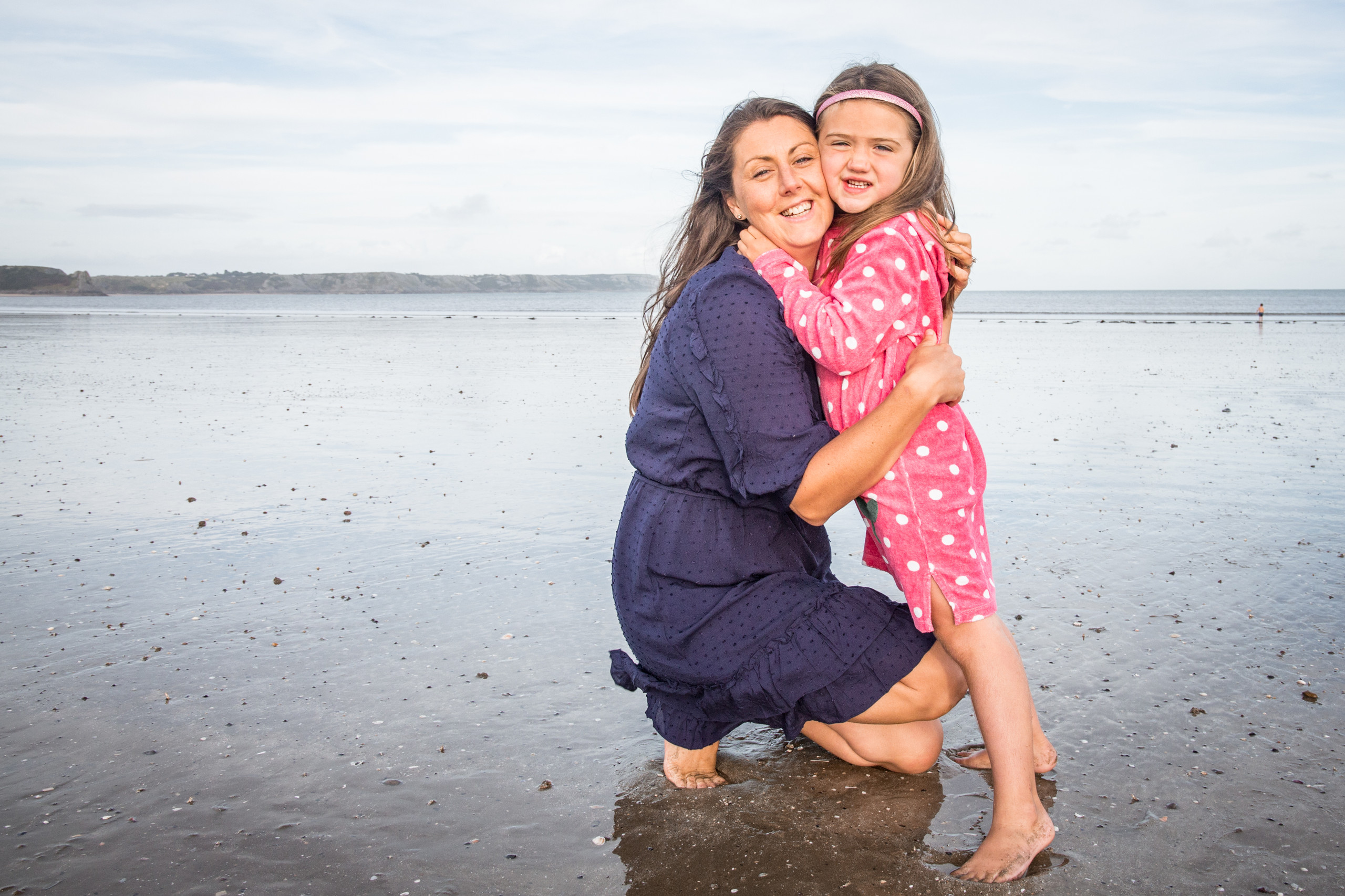 mother and daughter hug on oxwich bay