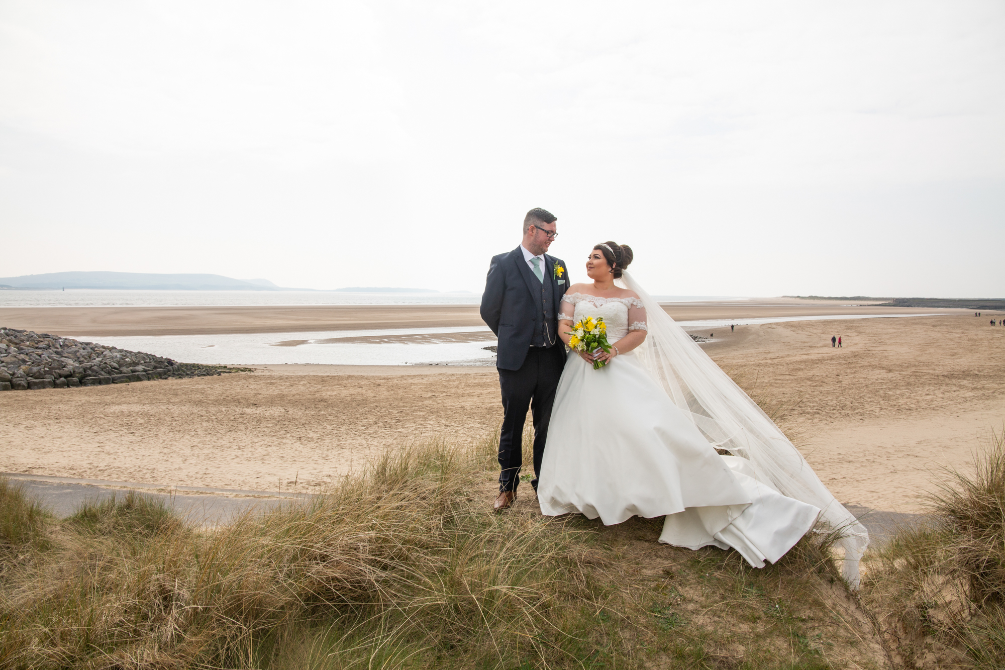 Burry Port Lighthouse Wedding Bride and Groom Looking at each OtherPhotography. A Beach Wedding Portrait. Photographer covering The Gower, Carmarthenshire, Llanelli, South Wales and Bridgend