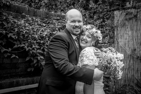 bride and groom from the gower embrace in a black and white picture