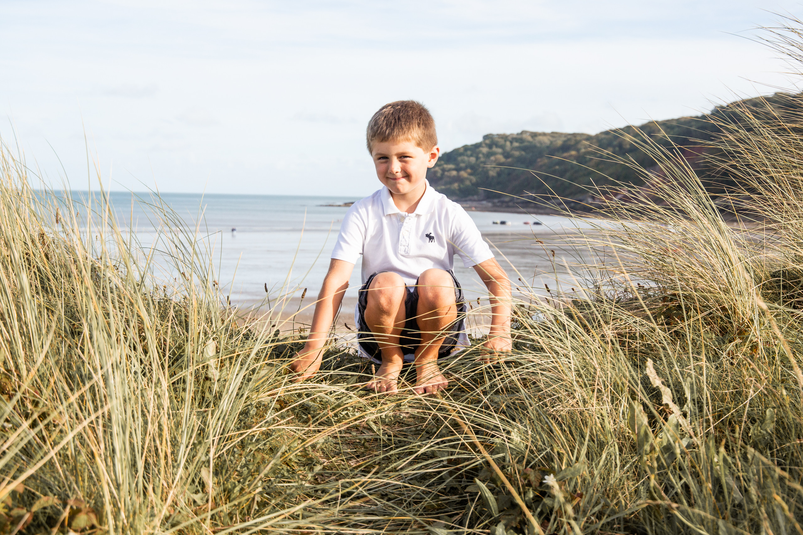 boy poses happily in the dunes at oxwich bay