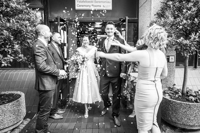 black and white photography of bride and groom under confetti in swansea bay