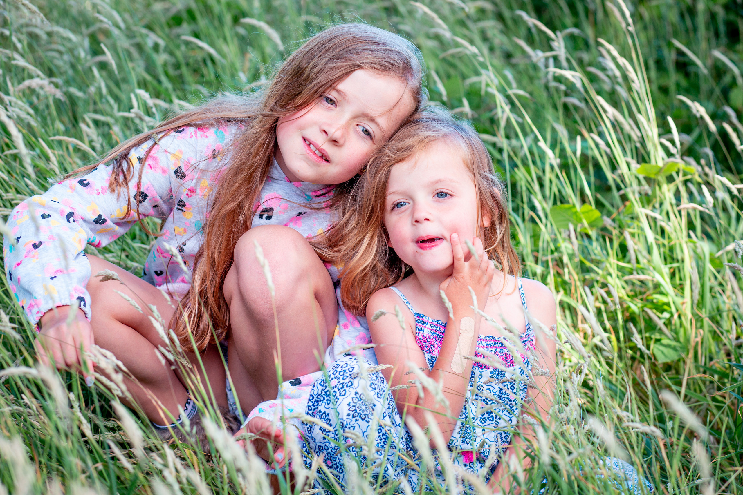 sisters take a moment to reposition themselves for swansea photographer