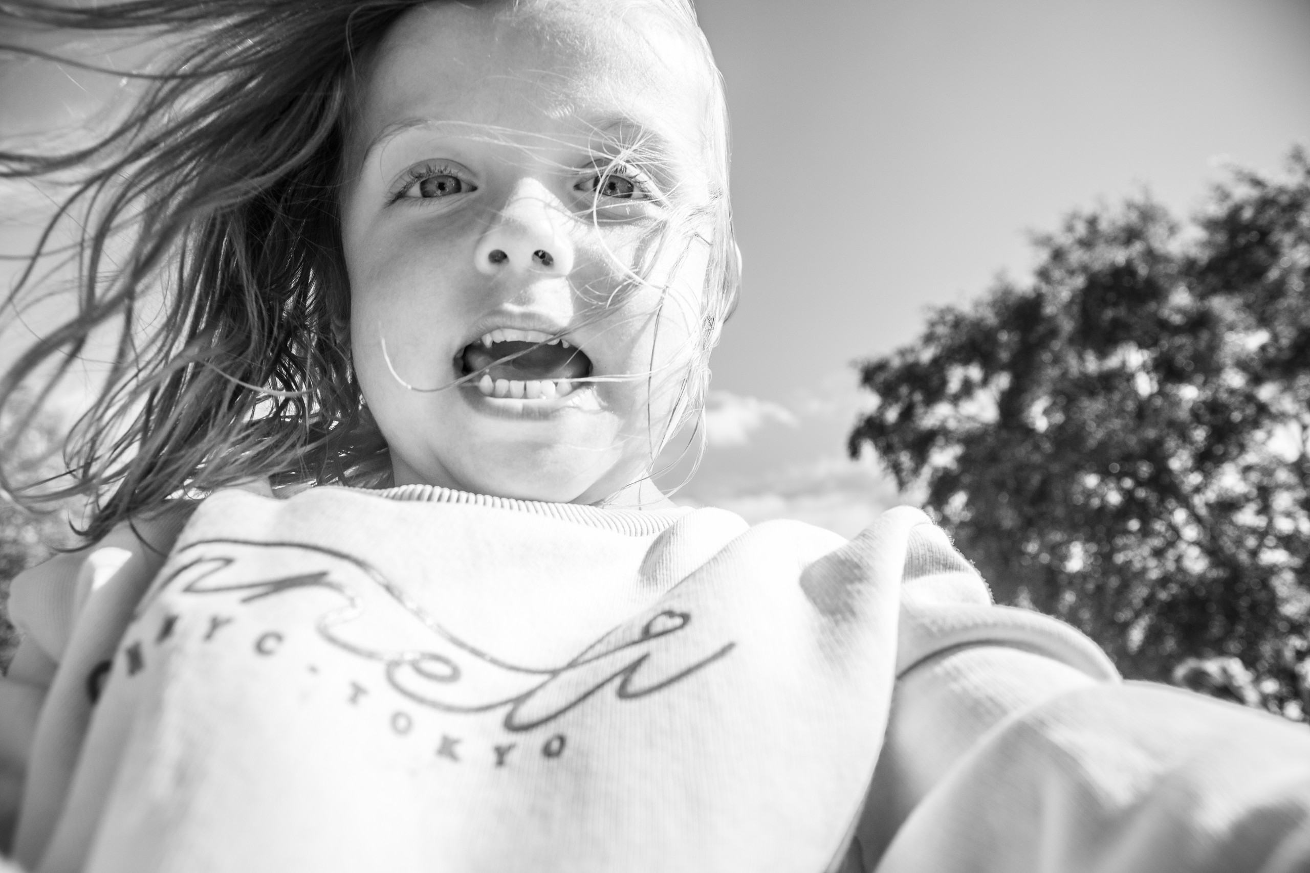 excited girl as she plays with the photographer in a swansea park