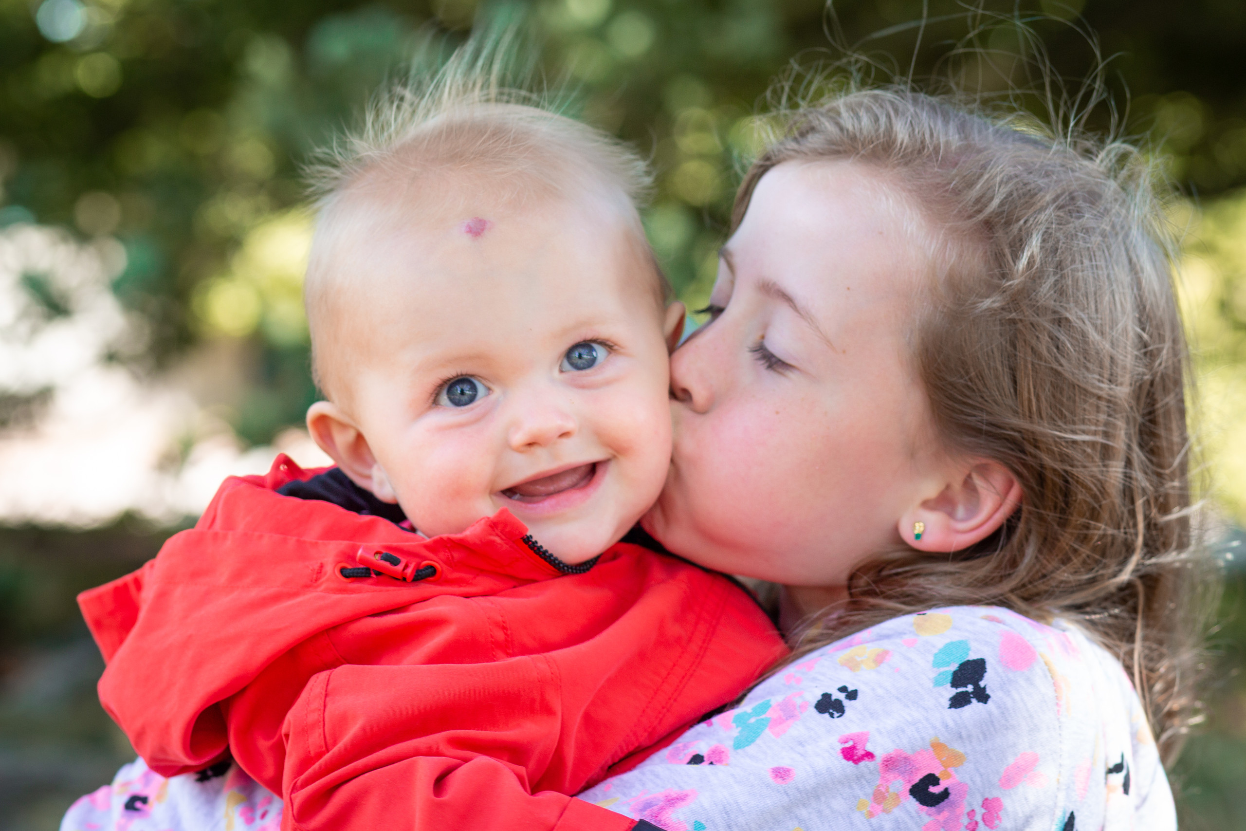 big sister gives little brother a kiss in a swansea park