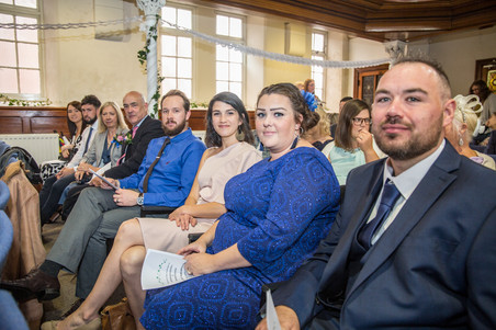 Guests smile for at a church wedding before swansea bride enters