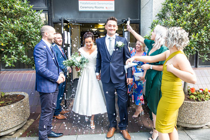 bride and groom exit swansea civic centre as newly weds smiling to photographer