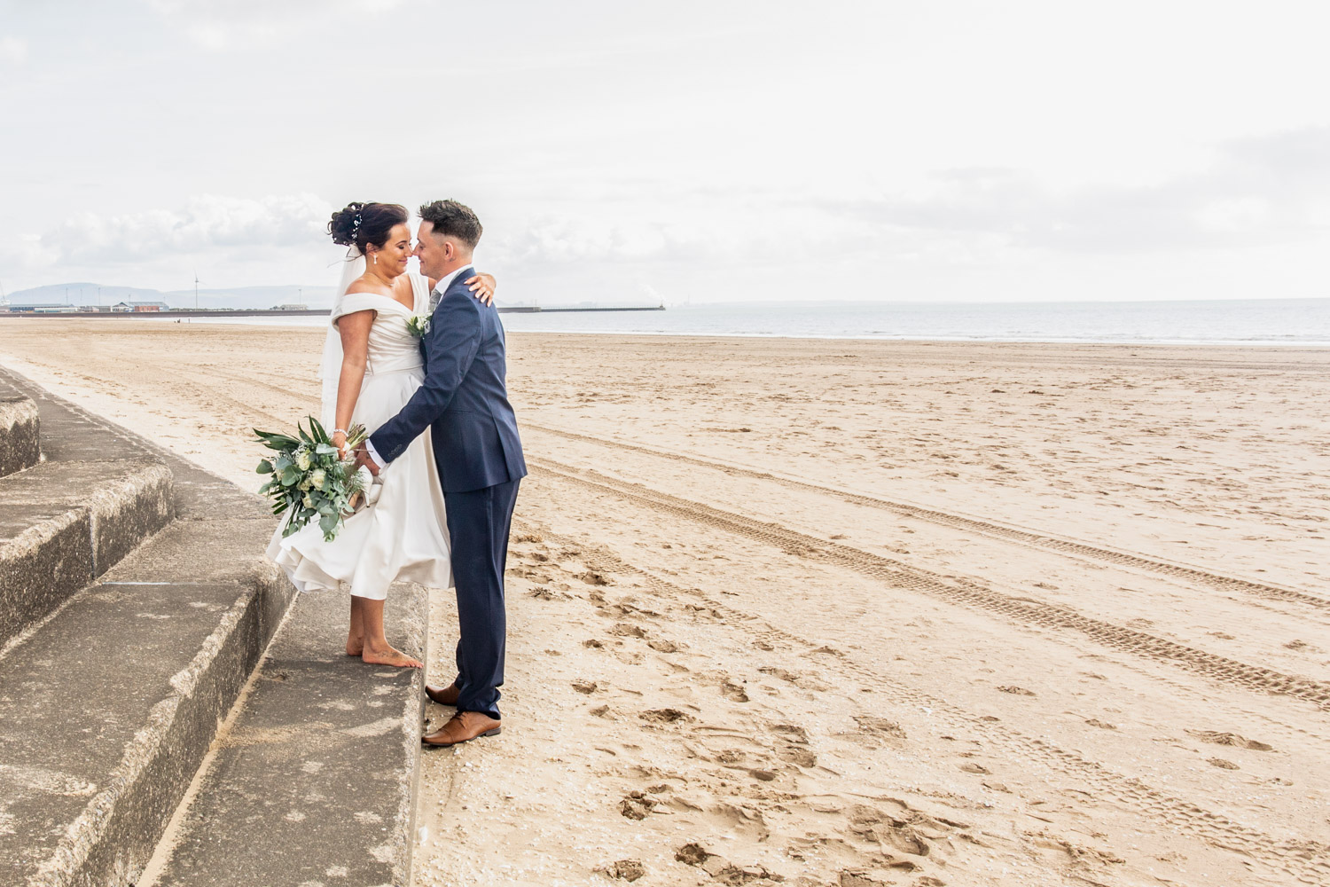 wedding photography of bride and groom on swansea bay with swansea in the background