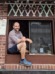 Marc Flore smiling sitting in ice cream window