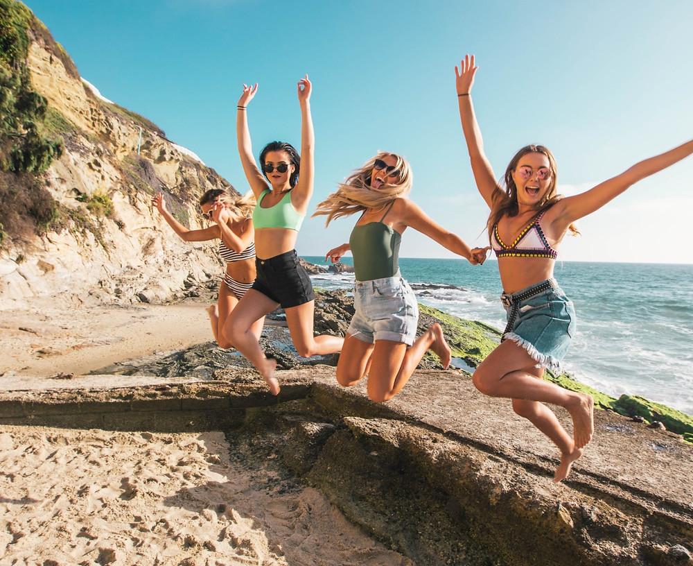 Cuatro chicas saltan en la playa
