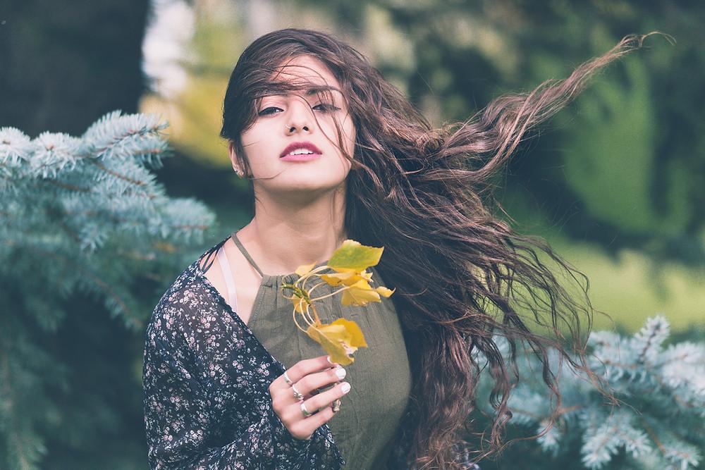 Chica sostiene hojas en la mano al aire libre en Canadá