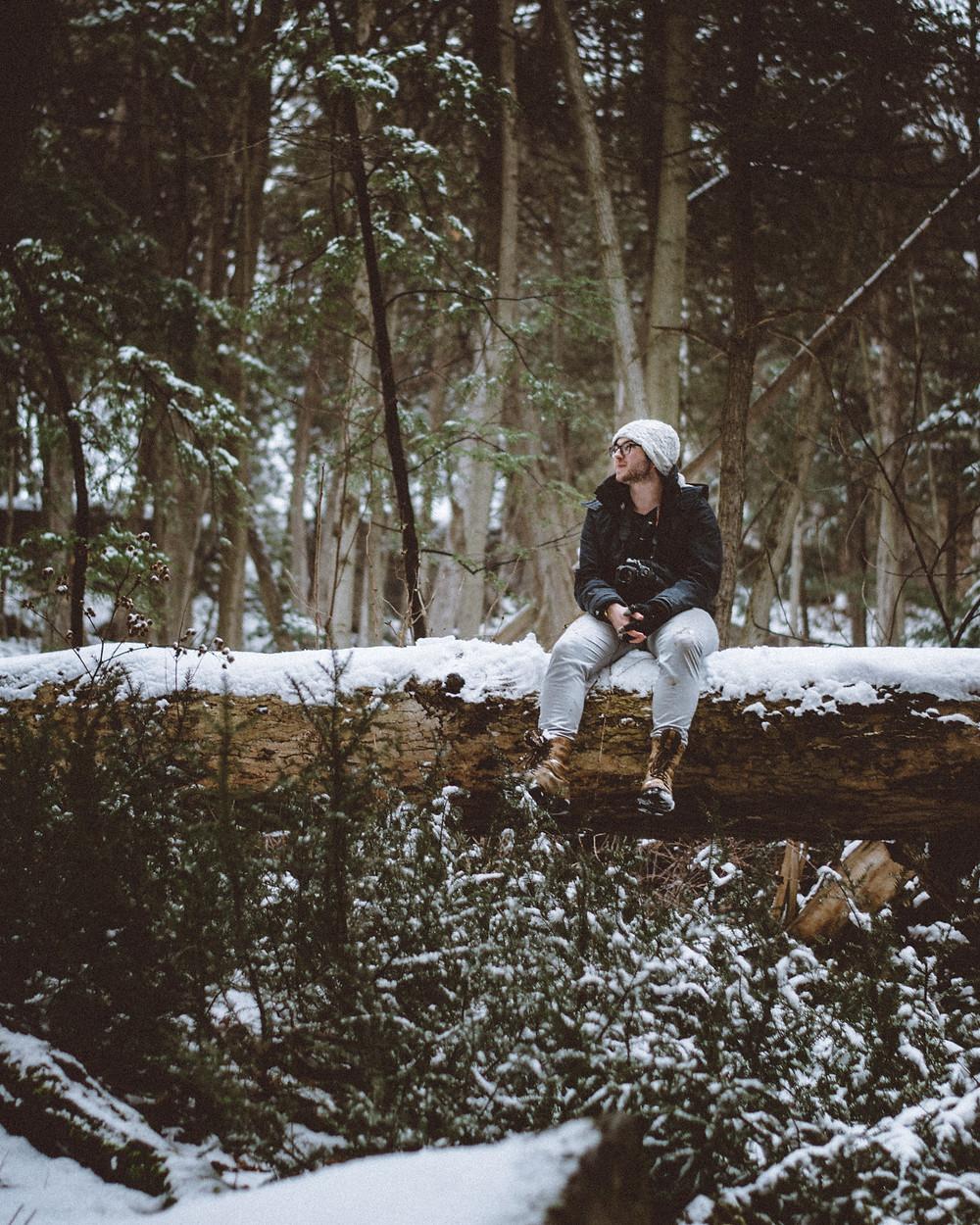 Hombre sentado sobre un tronco en bosque nevado