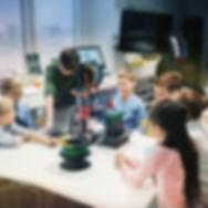 Kinder um einen 3D-Drucker