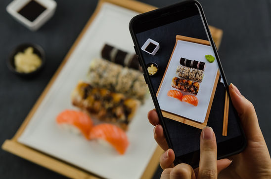 Young woman taking photo of sushi plate