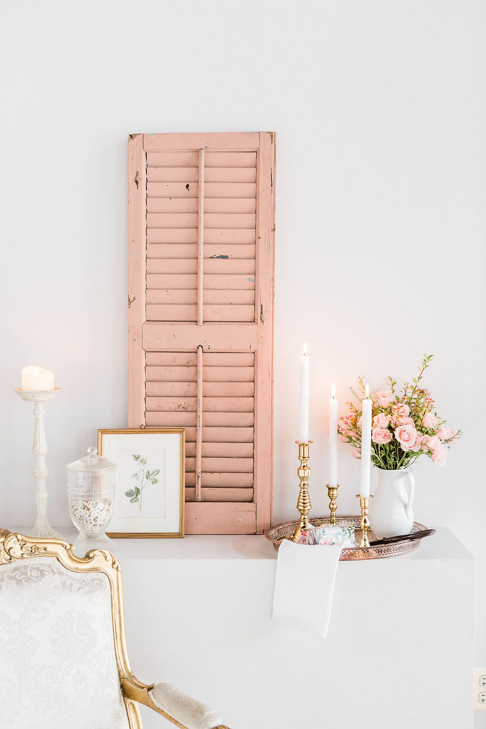Pink shutter sets the tone for the French-style seating area with chair and vintage accent pieces