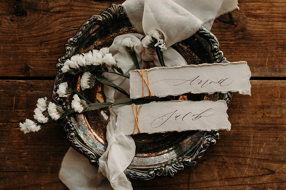 Silver vintage bowl holds name cards and a floral stem.