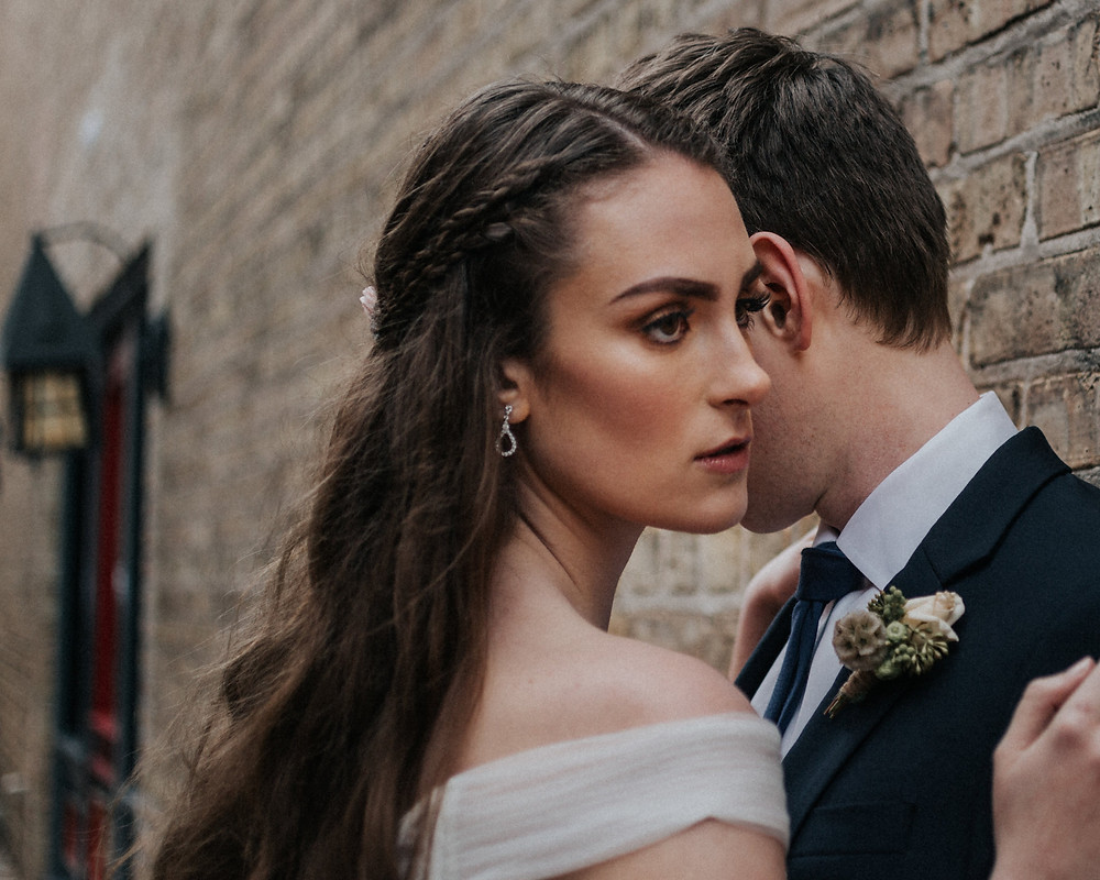 outdoor street-side bride and groom photo against brick building
