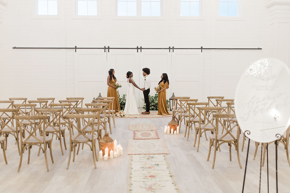 ceremony area at luxury barn venue in Northern IL with rug runners and vintage wine bottle decor