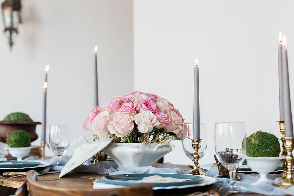 Farm table filled with vintage decor elements, including milk glass, vintage china tureen holding roses, and brass candleholders adds vintage charm