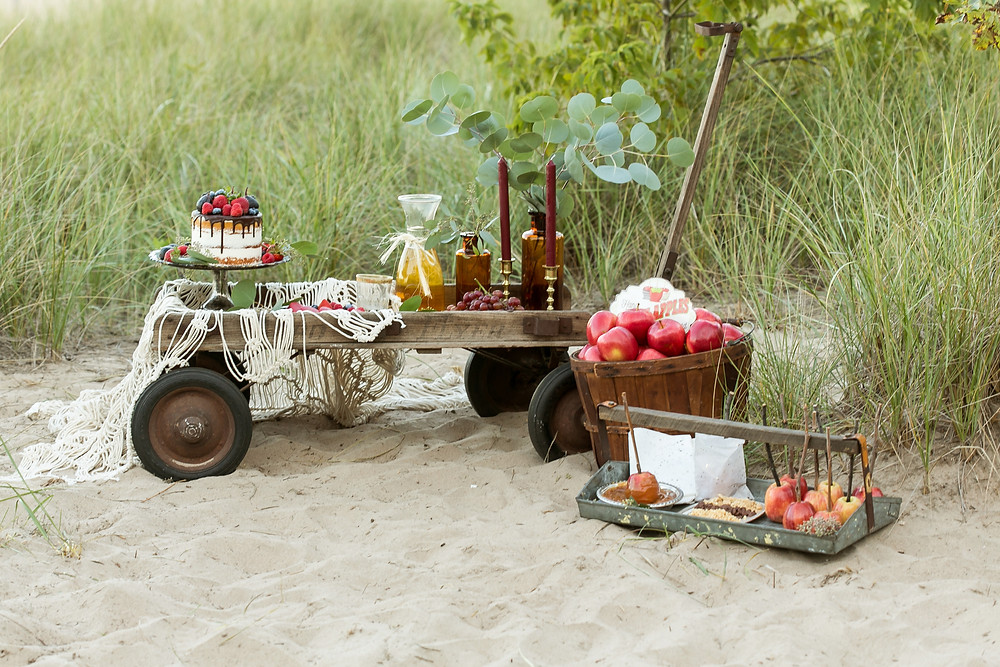 Berry basket holds caramel apples, while vintage wagon holds sweets and drinks