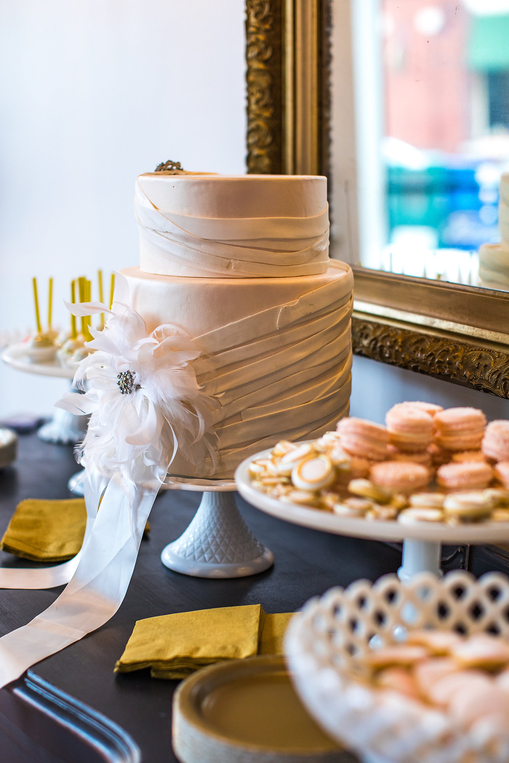 Wedding cake displayed on white milk glass cake plate, amongst other sweets on dessert table
